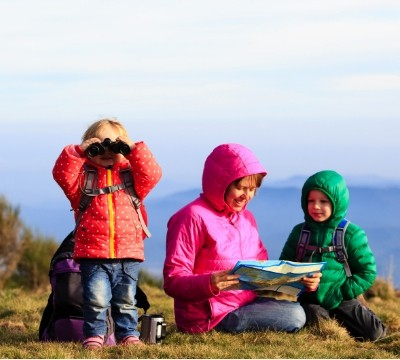 Kids on hike with map and binoculars