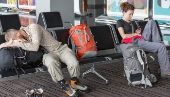 Tired backpackers at airport