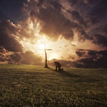 Kneeling at cross adventure with God