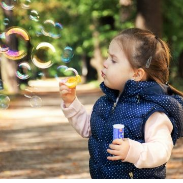 Child blowing bubbles outside