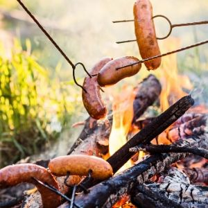 Cook hot dogs over campfire at home