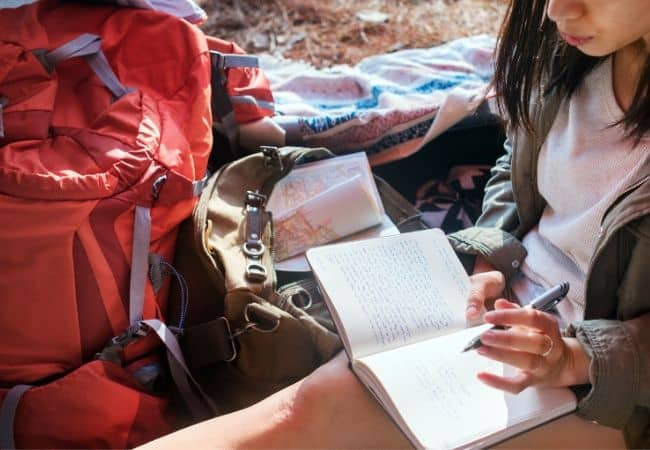 Girl writing in prayer journal camping