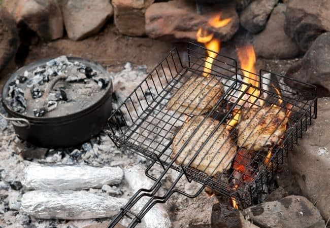 Cooking in dutch oven and grilling basket over campfire